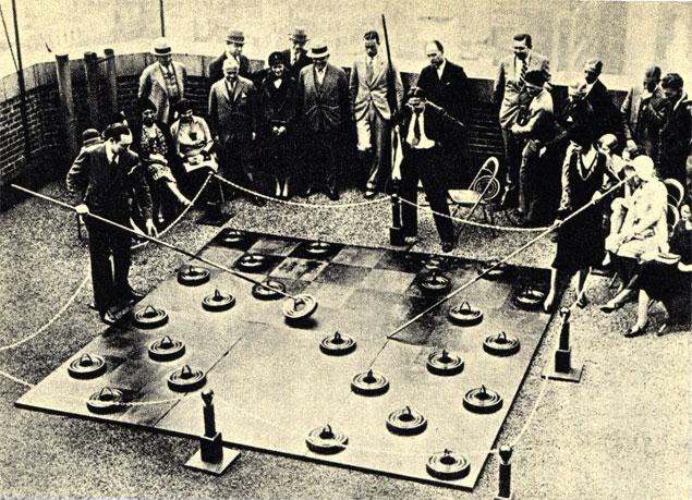 Оригинальная партия в шашки на веранде гостиницы. На этот раз от играющих пребуется также и физическое усилие. Фотография 1929 года