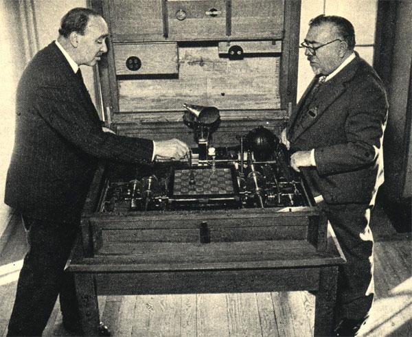 Электромагнитный 'игрок в шахматы' Гонзалеса Торреса И. Квеведо демонстрировался на конгрессе кибернетиков в Париже в 1951 году. На снимке: сын изобретателя показывает автомат выдающемуся ученому, создателю кибернетики, Норберту Винеру (справа)
