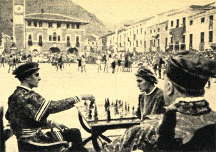 За шахматной доской сражаются два соперника, борющиеся за руку прекрасной Элеоноры, а ходы противников повторяют на рыночной площади 'живые шахматы'
